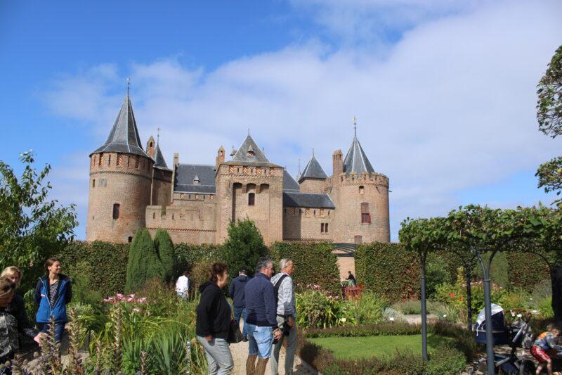 Bezoekers in kasteeltuin kasteel achtergrond