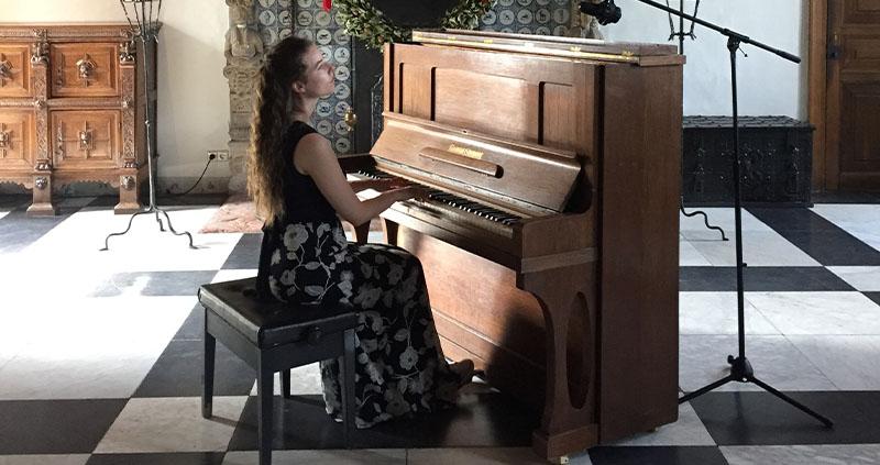 muzikant speelt piano in de ridderzaal van het Muiderslot
