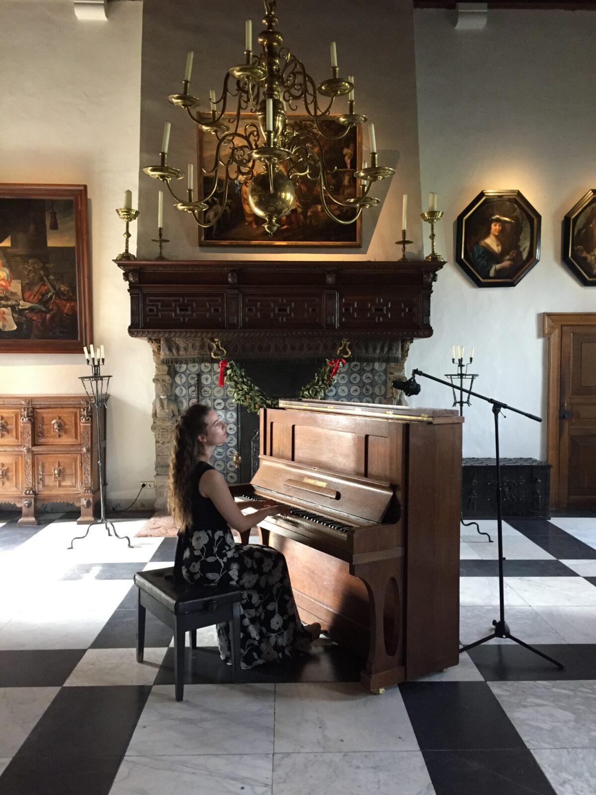 Anne Maartje speelt de piano in de Ridderzaal van het Muiderslot