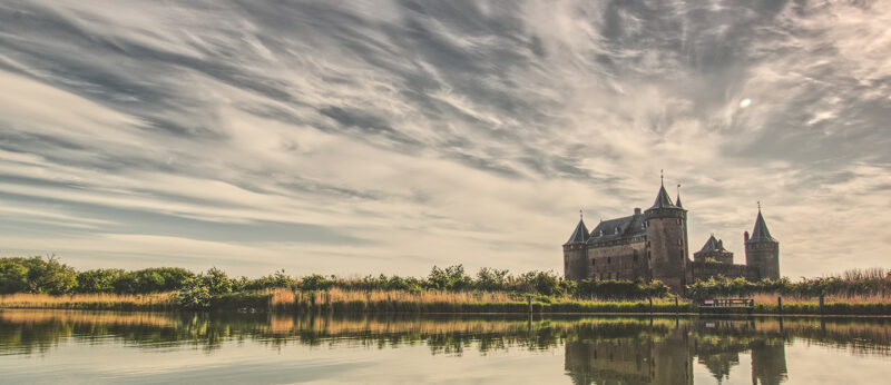 een uitzicht over de vecht met kasteel Muiderslot op de achtergrond